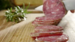 An experienced chef in a professional kitchen cuts the seasoned.Il Italian salami sausage is cut with a professional knife with very thin slices.