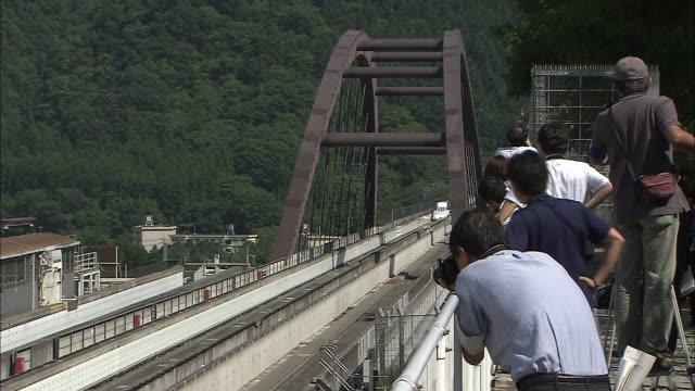 vidéos et rushes de an experimental maglev train speeds past photographers on a trial run - préfecture de yamanashi