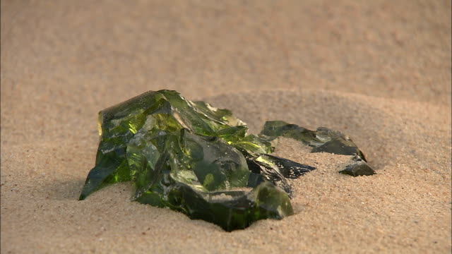 an explorer cautiously removes a piece of green glass from the sand. - 宝探し点の映像素材/bロール