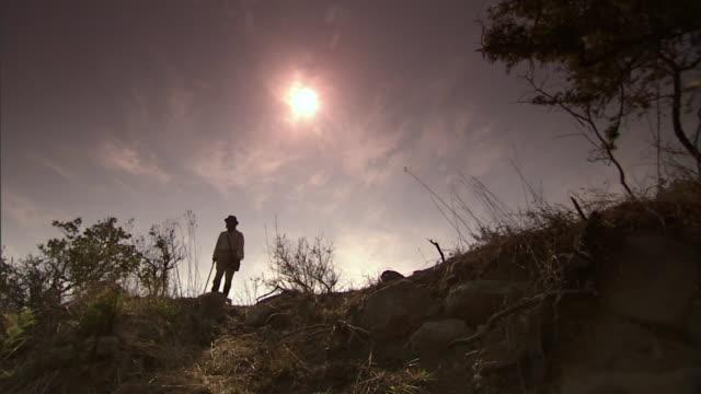 vídeos de stock e filmes b-roll de an explorer leads a procession of natives up a ridge. - explorador