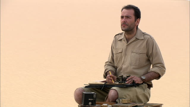 vídeos de stock e filmes b-roll de an explorer makes notes on charts and uses binoculars. - explorador