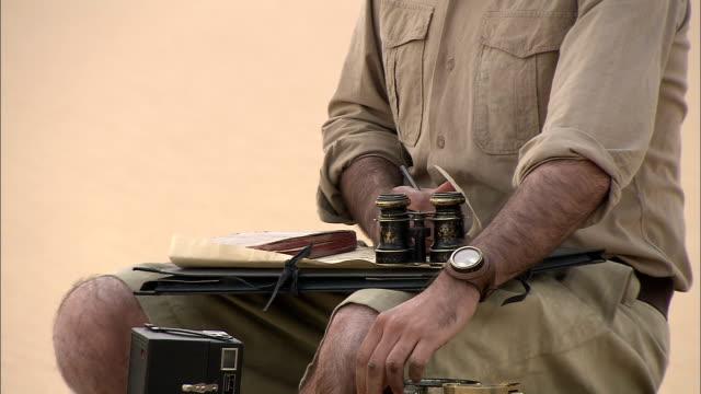 vídeos de stock e filmes b-roll de an explorer makes notes on charts and uses old-fashioned binoculars. - explorador