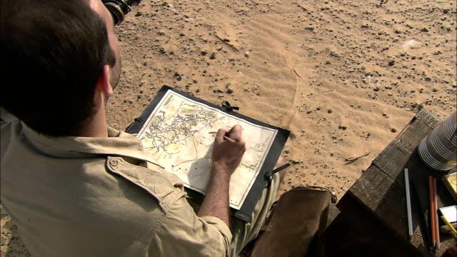 an explorer marks a map as he uses binoculars to observe the desert. - 探検家点の映像素材/bロール