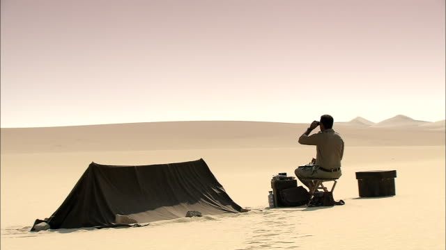 vídeos y material grabado en eventos de stock de an explorer uses binoculars to scan the desert as he sits on a folding chair. - silla plegable