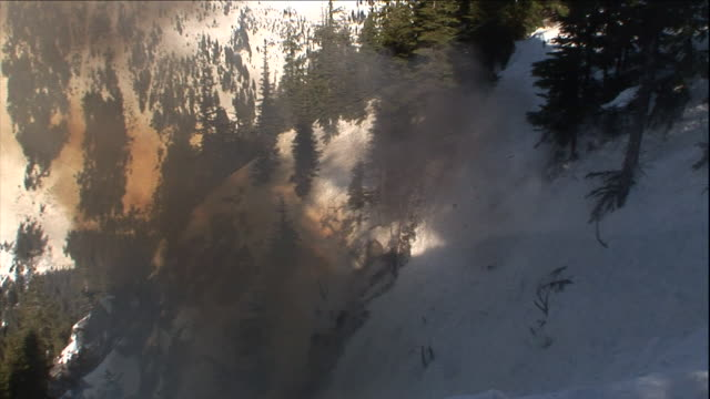 an explosion throws dirt and rubble from a snowy mountainside. - rubble stock-videos und b-roll-filmmaterial