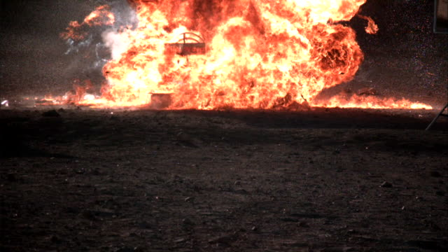 an explosions casts a fireball into a field. - fireball stock videos & royalty-free footage