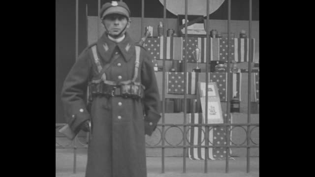 an expressionless soldier stands in front of a store featuring american flags; he turns right, fumbles with his sword, and stiffly moves right /... - blank expression stock videos & royalty-free footage