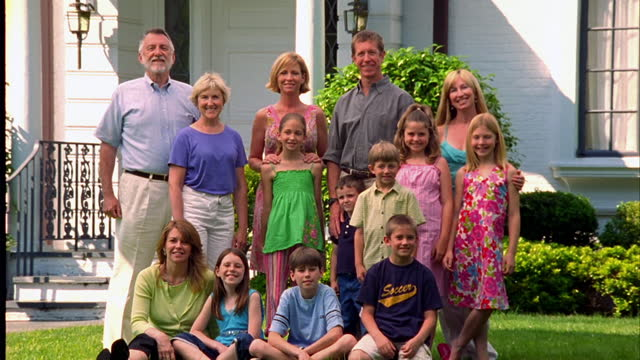 an extended family poses in a suburban front yard. - large family stock videos & royalty-free footage