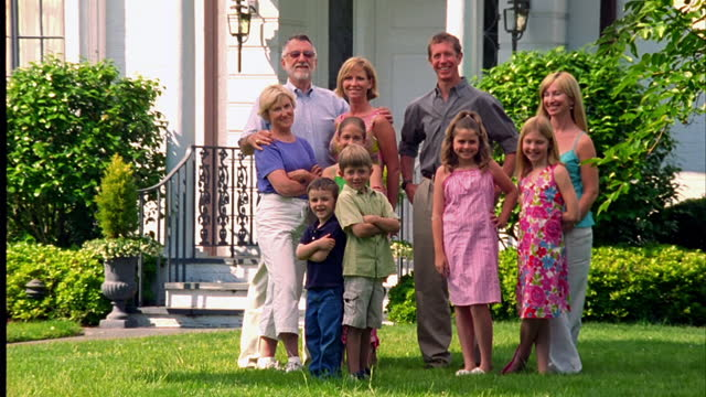 an extended family poses in a suburban front yard. - familie mit mehreren generationen stock-videos und b-roll-filmmaterial