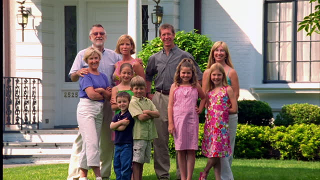 An extended family poses in a suburban front yard.