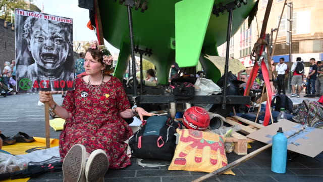 an extinction rebellion protestor is seen handcuffed to a green boat on duke street outside cardiff castle as the environmental protest group ends... - one young woman only stock videos & royalty-free footage