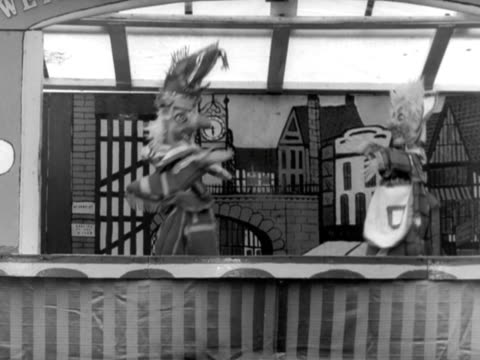 vidéos et rushes de an extract from a punch and judy show. mr punch and judy puppets dance and kiss one another before hitting each other with a stick. - marionnette