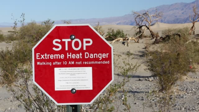 an extreme heat danger sign in death valley which is the lowest hottest driest place in the usa with an average annual rainfall of around 2 inches... - death valley national park stock videos & royalty-free footage