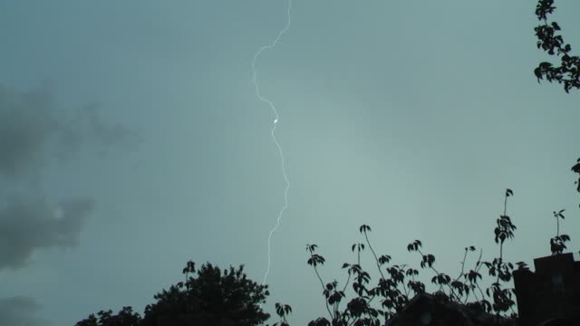 an extremely intense lightning bolt strikes the ground followed by very loud crashing thunder as a severe thunderstorm moves over a residential... - lightning strike stock videos and b-roll footage