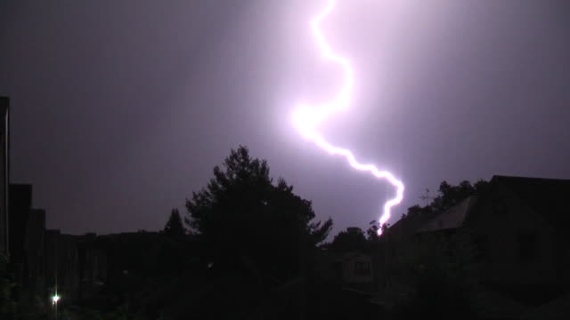 an extremely vivid lightning bolt illuminates the night sky and strikes the ground over a residential neighborhood in nyc as a severe thunderstorm... - lightning strike stock videos and b-roll footage