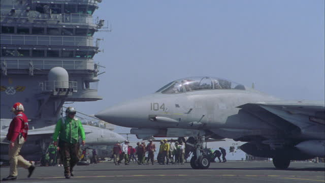 an f-14 tomcat lands on the deck of the uss john c. stennis and taxis for parking. - warship stock videos & royalty-free footage