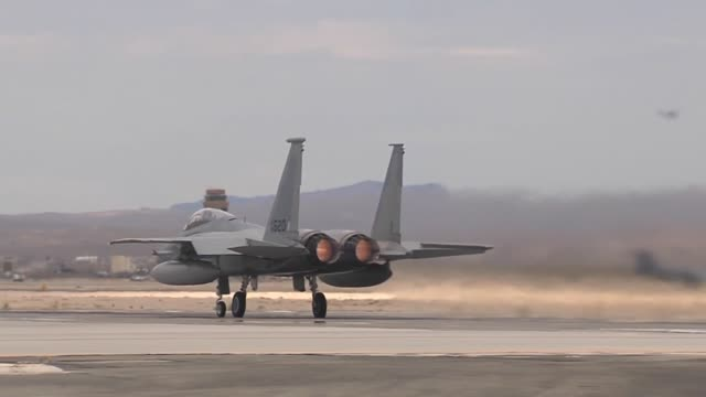 vídeos de stock, filmes e b-roll de an f15c assigned to the 65th aggressor squadron 57th wing at nellis air force base nev heads down the runway for takeoff during red flag 143 jul 16... - nellis air force base