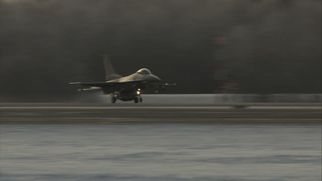 an f16 jet takes off from a snowy runway. - general dynamics f 16 falcon stock videos & royalty-free footage