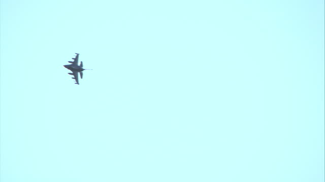 an f16 maneuvers across a blue sky. - fighter stock videos & royalty-free footage