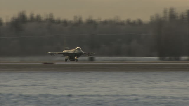 an f16 takes off from a snowy runway. - general dynamics f 16 falcon stock videos & royalty-free footage