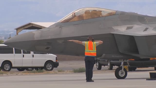 vídeos de stock, filmes e b-roll de an f22 completes final checks and is saluted by ground crew before taxiing to takeoff during red flag 143 jul 16 2014 at nellis air force base nev... - nellis air force base