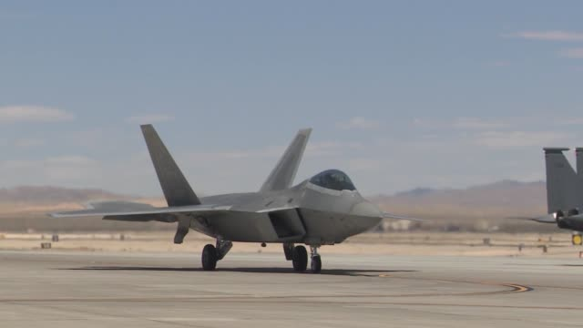 vídeos de stock, filmes e b-roll de an f22 raptor waits to taxi to the runway during red flag 143 jul 23 2014 at nellis air force base nev more than 440000 service members have... - nellis air force base