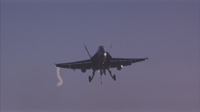 an fa-18 hornet fighter jet lands on an aircraft carrier. - aircraft carrier stock videos & royalty-free footage