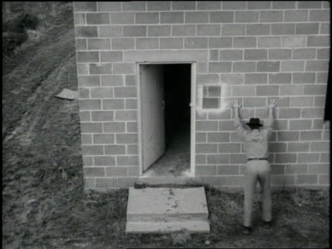 an f.b.i. agent speaks through a megaphone to a suspect in a building and the man exits and puts his hands against the wall. - fbi video stock e b–roll