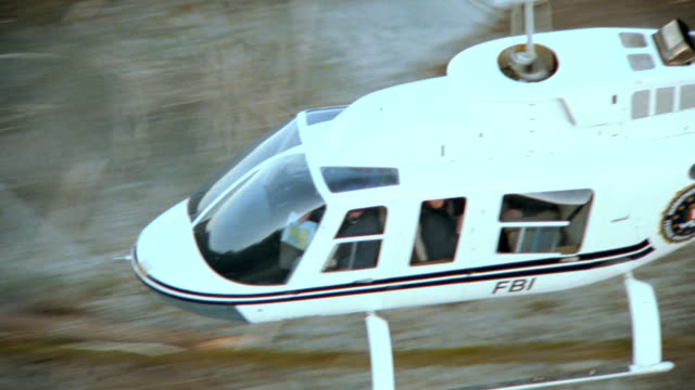 an fbi helicopter flies over a river and pine forest . - fbi stock videos & royalty-free footage