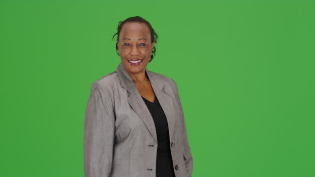 an happy african american businesswoman smiles on green screen - mature adult stock videos & royalty-free footage