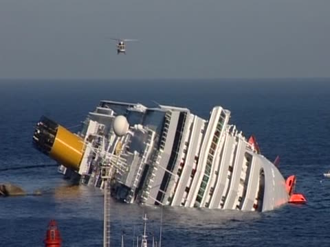 an helicopter flies over the cruise ship costa concordia capsized off the coast of isola di giglio. - sink stock videos & royalty-free footage