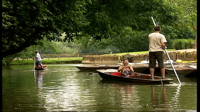 stockvideo's en b-roll-footage met oxford coot swimming along on river pan as disappears behind punt two punts along on river high angle shot punt towards as approaching bridge man... - koet