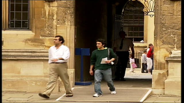 oxford radcliffe square ext tourists standing in square two men towards through arch from bodleian library low angle walls of library plaque over... - pembroke video stock e b–roll