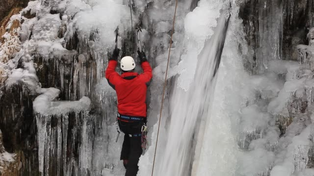 an ice climber on a waterfall in fisherplace ghyll frozen in the winter time, thirlmere, lake district, uk. - falling water stock videos & royalty-free footage