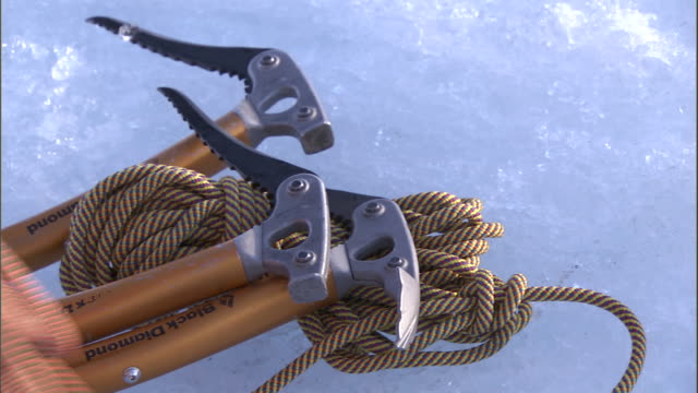 an ice climber readies rope and ice hammers on a snow bank. - climbing equipment stock videos & royalty-free footage