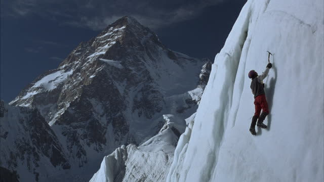 an ice climber scaling an ice wall with ice axes and crampons and a barren mountain ridge in the background. - rock climbing stock videos & royalty-free footage
