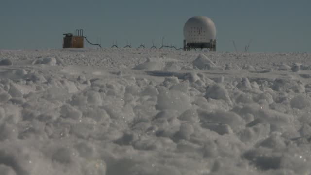 An ice station stands in solitude on a vast snowfield in Antarctica. Available in HD.