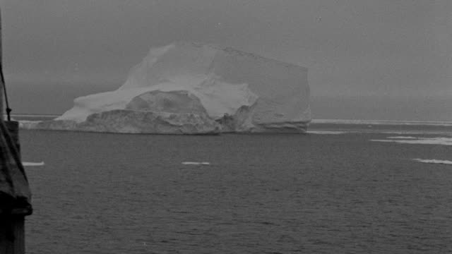 an iceberg drifts near the bow of a sailing ship during a richard e. byrd polar expedition. - black and white stock videos & royalty-free footage