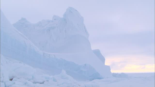vídeos de stock, filmes e b-roll de an iceberg on the snow-covered ground in the north pole - pólo norte