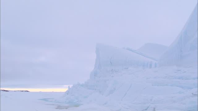 vídeos de stock e filmes b-roll de an iceberg on the snow-covered ground in the north pole - clima polar