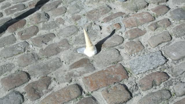 an ice-cream dropped onto a cobble floor - eis stock-videos und b-roll-filmmaterial
