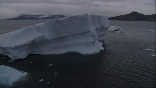 an icy sea flows around an iceberg near coast in antarctica. - bbc stock videos and b-roll footage