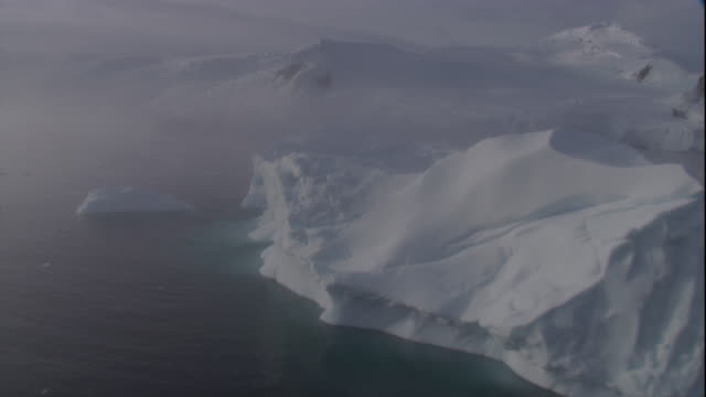 an icy sea separates an iceberg and a crumbling ice shelf in antarctica. available in hd - antarctica iceberg stock videos & royalty-free footage