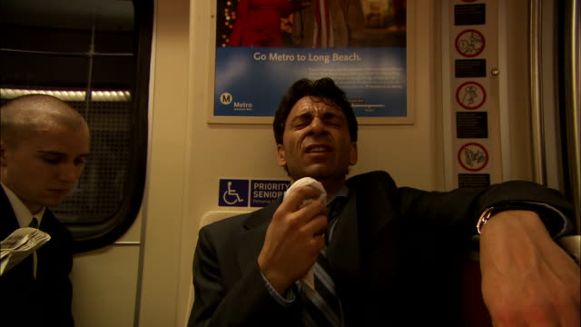 an ill businessman coughs and sneezes as he sits in a subway train. - 咳点の映像素材/bロール