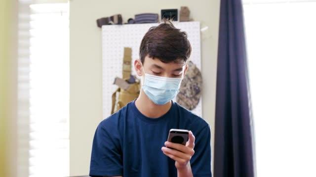 vidéos et rushes de un adolescent malade utilise le smartphone dans sa chambre - jeunes garçons