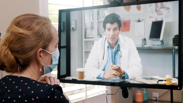 an ill woman talks with a doctor via telemedicine appointment - flat screen stock videos & royalty-free footage