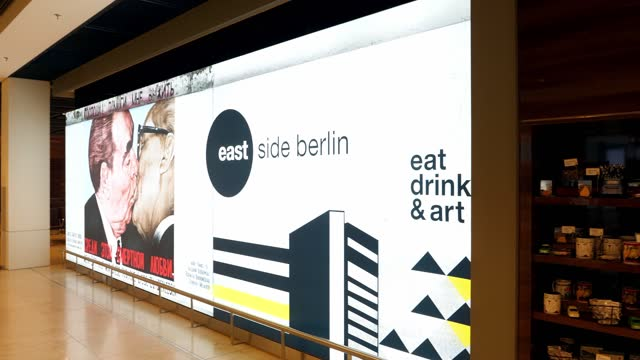 an illuminated billboard shows a photograph of a piece of the east side gallery from the former berlin wall in terminal 1 while shops stand open... - commercial sign stock videos & royalty-free footage