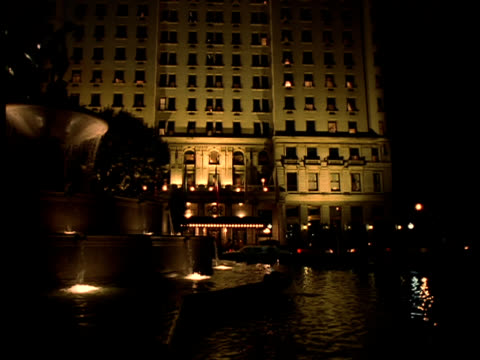 an illuminated fountain splashes in front of the plaza hotel in new york city. - film montage stock videos & royalty-free footage