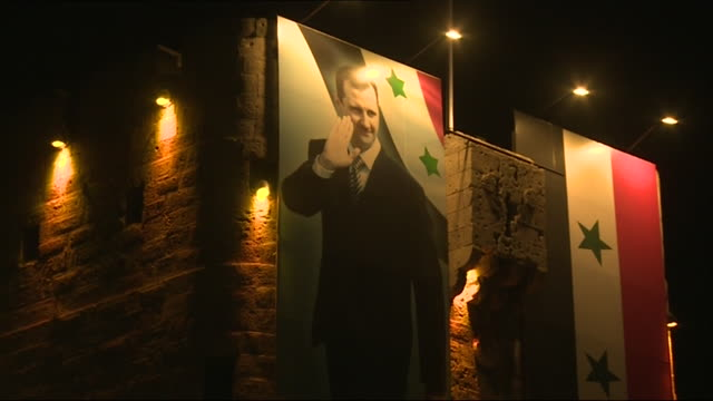 an illuminated poster of bashar alassad at the citadel of aleppo on syria's independence day - poster stock videos & royalty-free footage