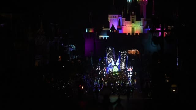 an illuminated tinker bell character flies in front of an illuminated float as visitors watch the disney paint the night nighttime spectacular parade... - parade float stock videos and b-roll footage